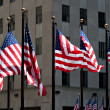 Flags of the United States for 4th of July in front of buildings - Stock Photo