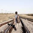 Teen boy walking on rail road — Stock Photo #7005453