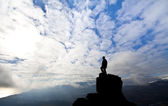 Woman on top of the mountain reaches for the sun — Stock Photo
