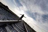 Silhouette of man walking on rail road — Stock Photo