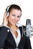Smiling woman in front of a microphone headset — Stock Photo