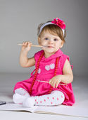 Seated little girl holding a paintbrush — Stock Photo