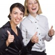 Stock Photo: Two smiling business women show a thumbs up