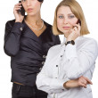 Two business women talking on mobile phone — Stok fotoğraf