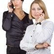 Two business women talking on mobile phone — Stockfoto