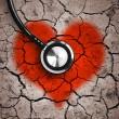 Heart in desert land and stethoscope — Stock Photo