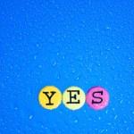 färg brev på blå bakgrund. ordet Ja — Stockfoto