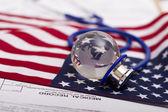 Stethoscope and globe on a USA flag — Stock Photo