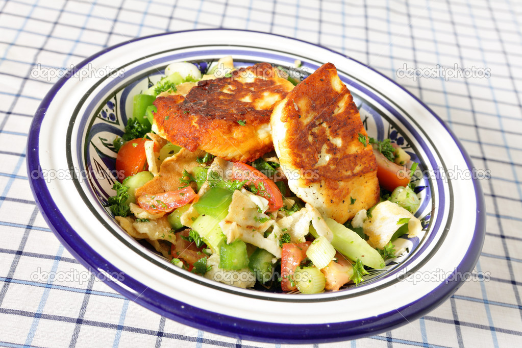 A bowl full of fattoush Middle Eastern salad topped with fried haloumi cheese. Fattoush is made with fried or toasted flat bread, chopped tomato, cucumbers, sca — Stock Photo #7021235