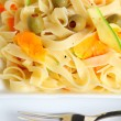 A plate of tagliatelle with ribbons of carrot and courgette - Stock Photo