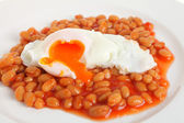 Poached egg on baked beans — Stock Photo