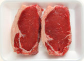 Two raw veal sirloin steaks on a supermarket butchers' tray — ストック写真