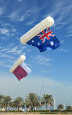 Australian and Qatari flags fly from tethered balloons above Doha, Qatar — Stock Photo
