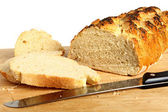 A loaf of homemade bread on a breadboard with a breadknife — Stock Photo