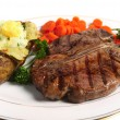 A dinner of a Porterhouse steak - Stock Photo