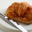 Croissant, white plate and knife — Stock Photo