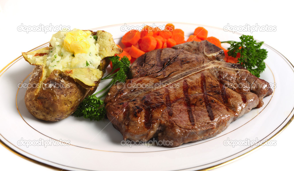 A dinner of a Porterhouse steak, with baked potato filled with mashed parsley potato topped with butter, served with sliced carrots and garnished with parsley  Stock Photo #7042247