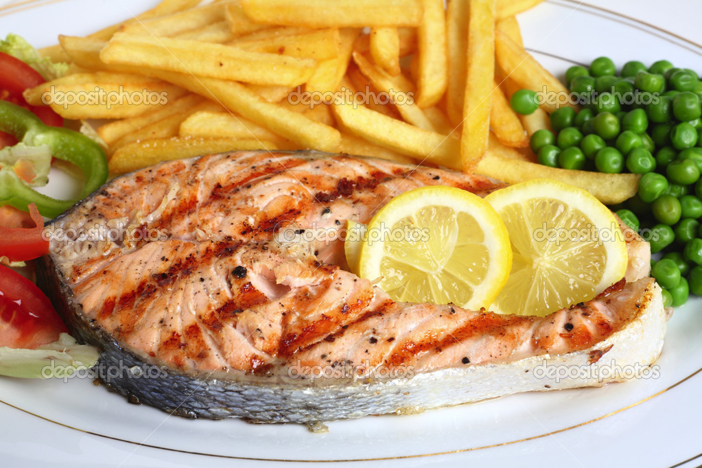 A close-up view of a grilled salmon steak served with salad, chips, peas and lemon slices. — Stock Photo #7042842