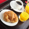 A continental breakfast of a croissant, black coffee and orange juice — Stock Photo