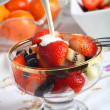 Cream being poured on Fresh fruit salad in a glass bowl — Stock Photo