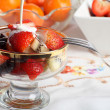 Royalty-Free Stock Photo: Cream being poured on Fresh fruit salad in a glass bowl