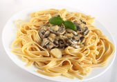 Mushrooms in cream on fettuccini — Stock Photo