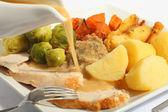 Pouring gravy on a roast turkey meal — Stock Photo