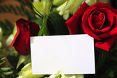Red roses, orchids and a blank card — Stock Photo