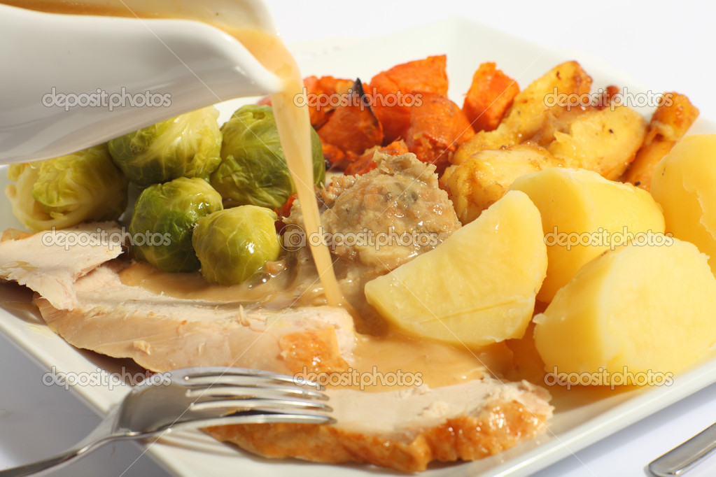 Pouring gravy on a festive turkey meal, with roast yams, roast parsnips, boiled potatoes and stuffing — Stock Photo #7054945