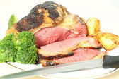 Roast sirloin beef joint with knife — Stok fotoğraf