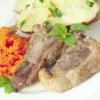Lamb chops carrots and baked potato — Stock Photo