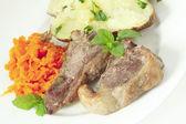 Lamb chops carrots and baked potato — Stock Photo