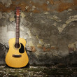 Acoustic guitar against grungy wall — Stock Photo #7104826