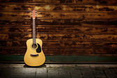 Acoustic guitar against rusty gates — Stock Photo