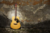 Acoustic guitar against grungy wall — Stock Photo