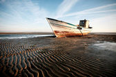 Aground boat on the beach — Stock Photo