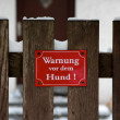 Sign on Fence in Winter Warning of Vicious Dog in German - Stock Photo