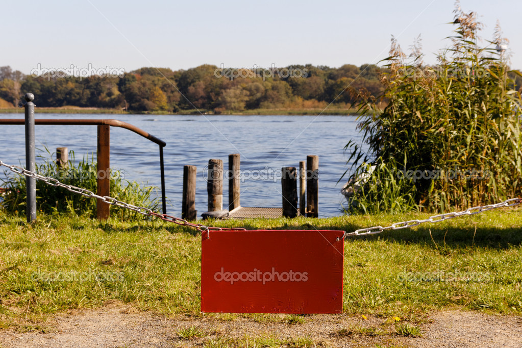 A red sign dangling from a chain closing off access to a lake in the background with a small boat landing (with copyspace). — Stock Photo #7192321