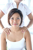 Asian woman receiving a shoulder massage — Stock Photo