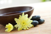 Spa setting with hot stones with chrysanthemum and bowl of water. — Stock Photo