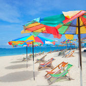 Colorful sun parasols and sundeck chairs on beautiful white sandy beach — Stock Photo