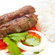 Delicious lamb seekh kebabs served with rice and tomatoes — Stock Photo
