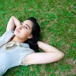 Young female laying on the grass, thinking — Foto de Stock