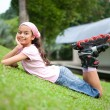 Young girl resting after rollerblading in the park — Stock Photo