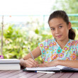 Stock Photo: Beautiful young girl doing her homework in a home environment