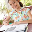 Beautiful young girl doing her homework in a home environment — Stock Photo