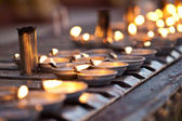 Oil lamps line the prayer wall — Stock Photo