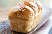 Delicious sweet brioche on wooden plate — Stock Photo