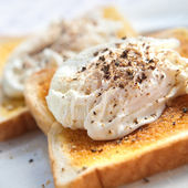 Delicious poached egg on buttered toast with freshly cracked black pepper — Stock Photo