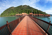 Walkway above water overlooking traditional resort chalet on a tropical island — Stock Photo
